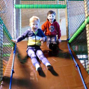 Jungen rutschen auf Kletterschräge im Sonnenlandpark