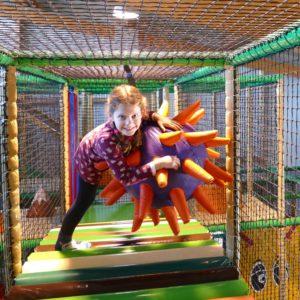 Mädchen spielen auf Igelball im Indoorspielplatz im Sonnenlandpark